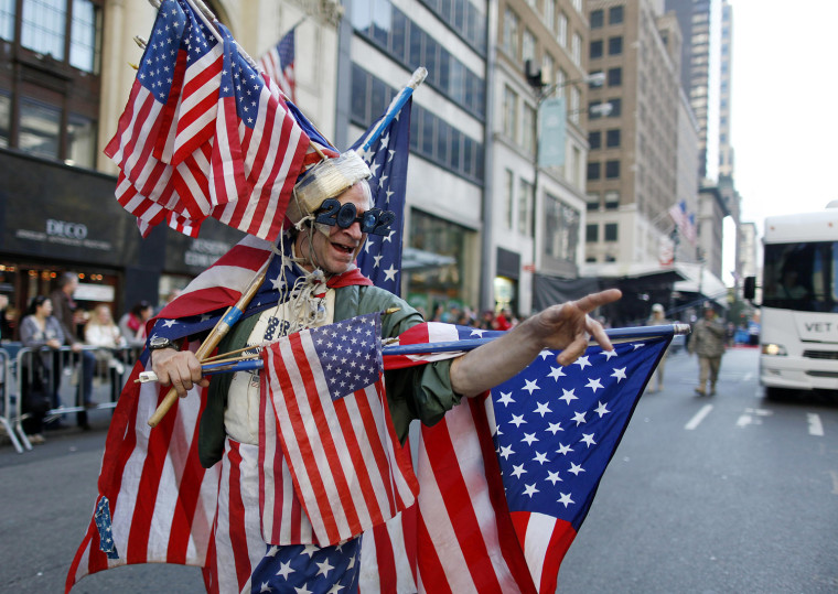 Image: A man adorned with American Flags marches up 5th Avenue during the Veterans Day Parade in New York