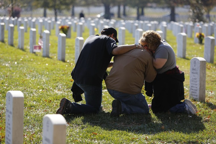 Image: People grieve at a gravesite during Veterans Day observances at Arlington National Cemetery in Arlington, Virginia