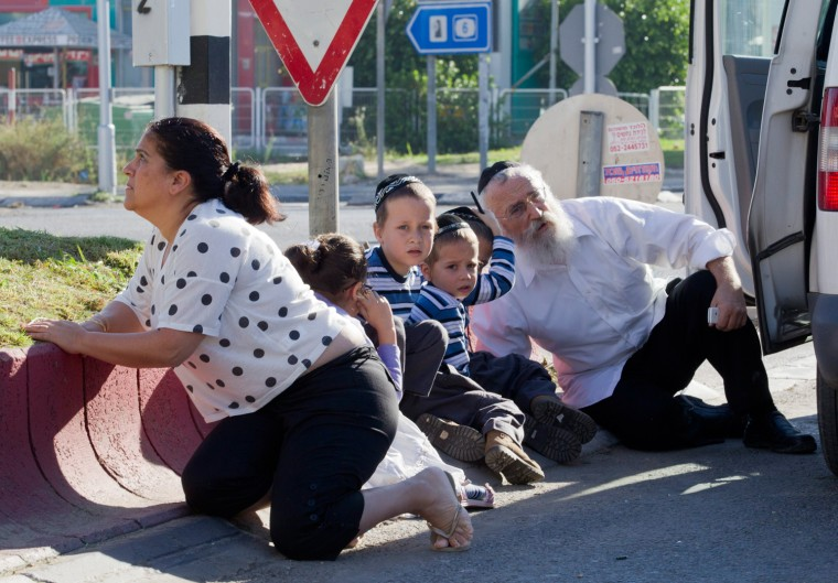 Image: Israelis huddle by a roadside as rockets are fired at Kiryat Malachai from the Gaza Strip