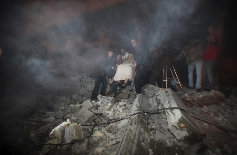 Image: Palestinians help to evacuate a woman following Israeli air strikes in Gaza