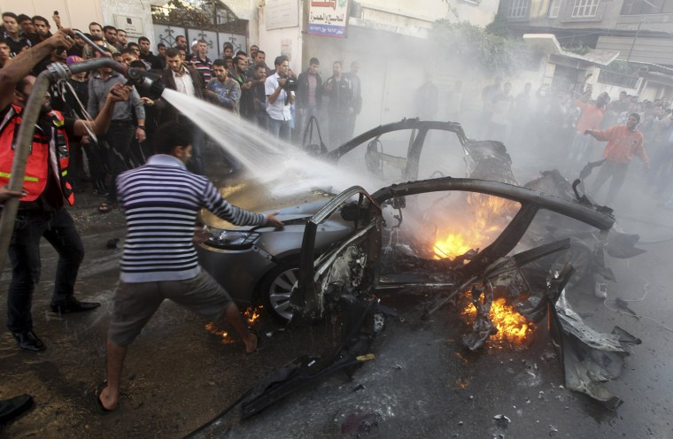 Image: Palestinians help extinguish the fire after an Israeli air strike on the car of Hamas's top commander in Gaza City