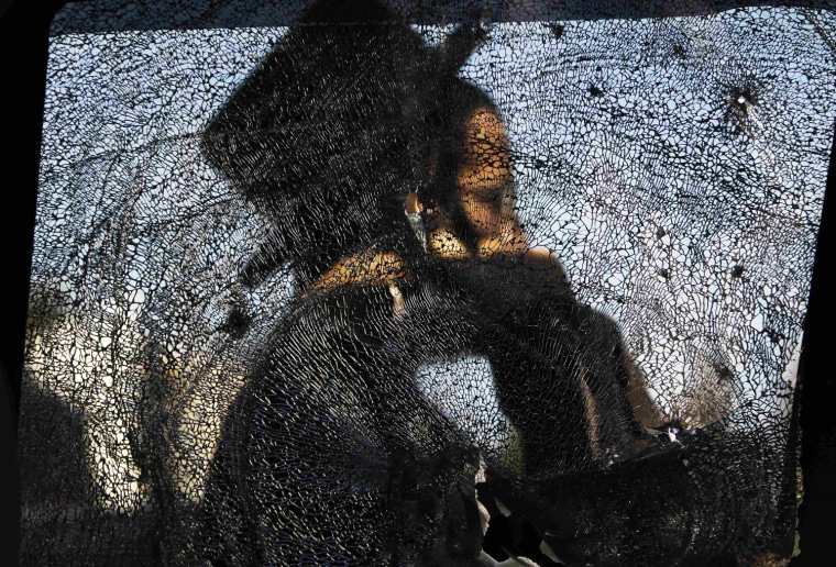 Image: Ultra-Orthodox Jewish man is seen through a damaged car window after a rocket fired from Gaza landed in Ashdod