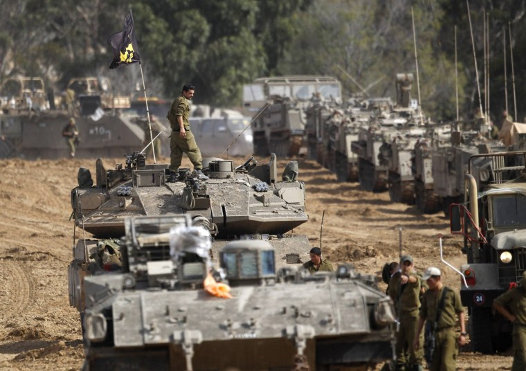 Image: Israeli soldiers prepare armoured personnel carriers at an area near the border with the Gaza Strip