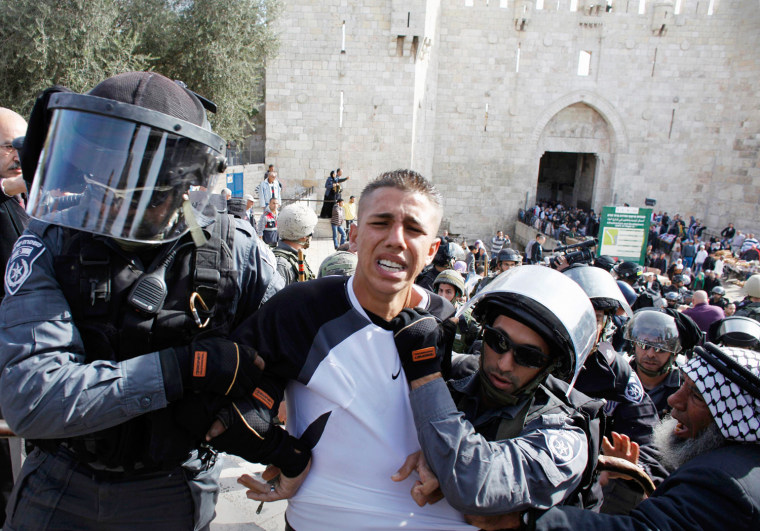 Image: Israeli border police officers detain a Palestinian demonstrator during clashes after a protest against Israel's military operation in Gaza, outside Damascus Gate in Jerusalem's Old City