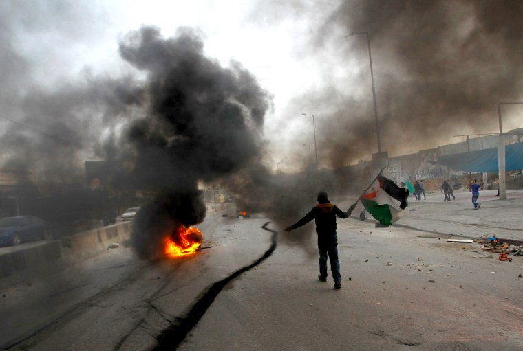 Image: A Palestinian stone-thrower walks past smoke from burning tyres during clashes with Israeli security forces against Israel's military operation in Gaza, near Ramallah
