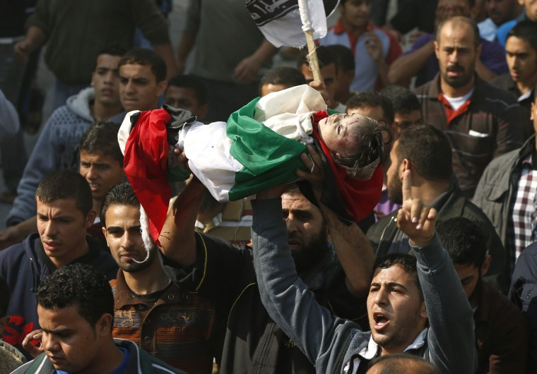 Image: Palestinians carry the body of a child from the al-Dalo family during a mass funeral in Gaza City