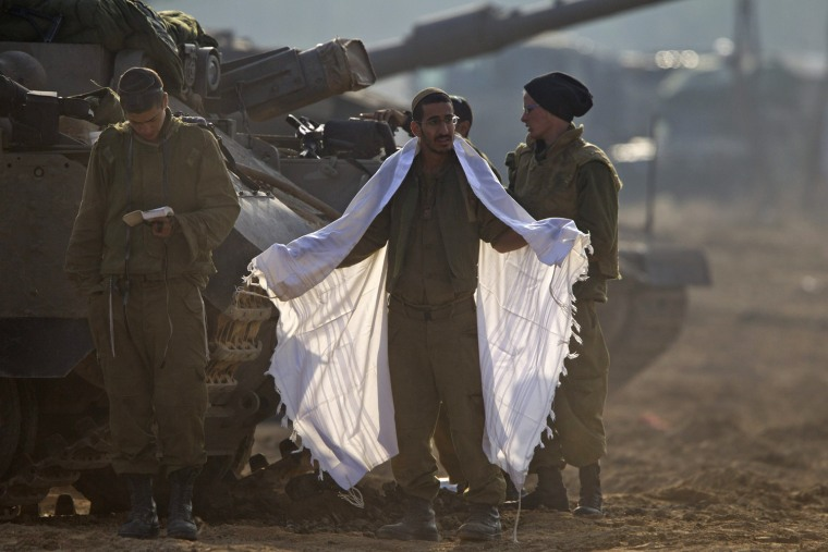 Image: Israeli soldiers at a tank staging area along Gaza Strip border