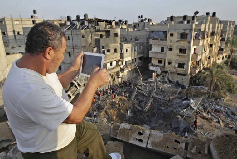 Image: Palestinian man takes pictures of a destroyed house after an Israeli air strike in Khan Younis in the southern Gaza Strip
