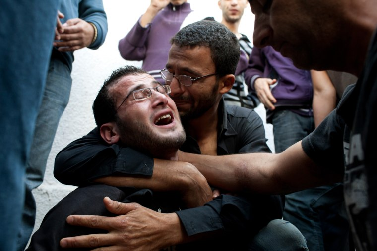 Image: Family members and friends react during a funeral for several members of a family whose home was bombed in Gaza City.
