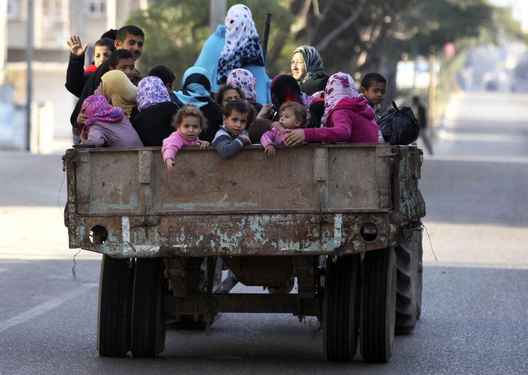 Image: Displaced Palestinians ride in a flatbed truck as they make their way to a U.N.-run school in Gaza City