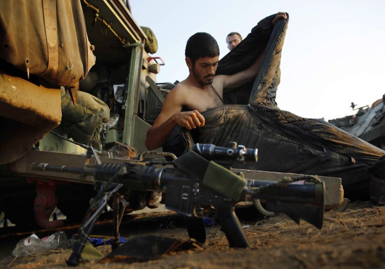 Image: Israeli soldier gets out of his sleeping bag at a staging area near border with Gaza