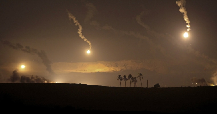 Image: Parachute Israeli flares illuminate the area for an artillery barrage on Israel's border with the Gaza Strip