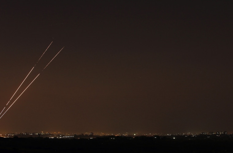 Image: Rockets streaks are seen in the night sky after they are launched from the northern Gaza Strip towards Israel