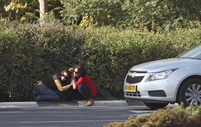 Image: Israeli woman take cover as a siren warning of incoming rockets sounds in Jerusalem