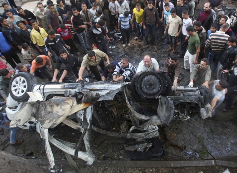 Image: Palestinians gather around a destroyed car after what witnesses said was hit by an Israeli air strike in Gaza