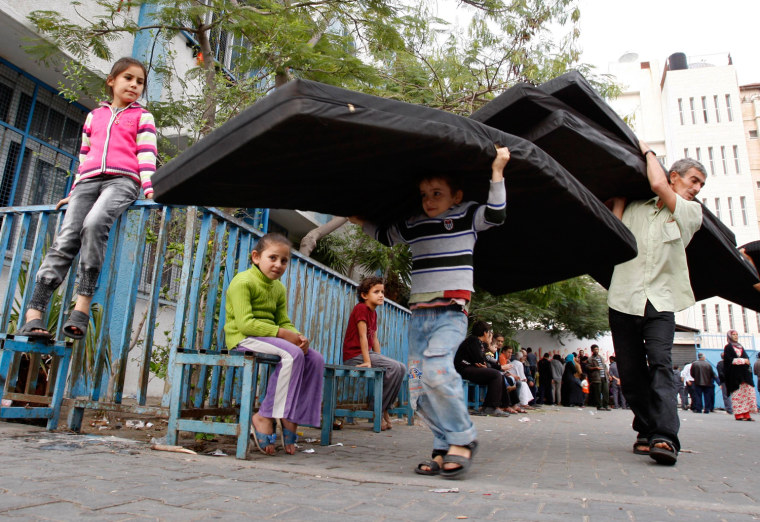Image: Displaced Palestinians carry mattresses distributed by the UNRWA at a school in Gaza City