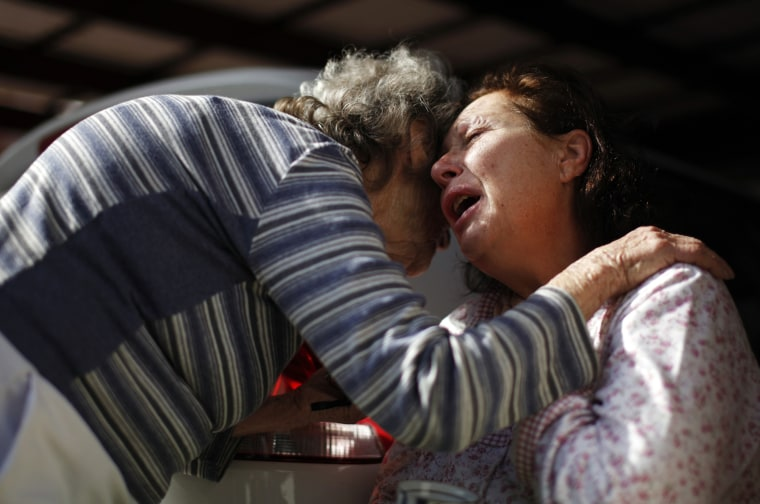 Image: A wounded Israeli woman is comforted at the scene east of Ashdod