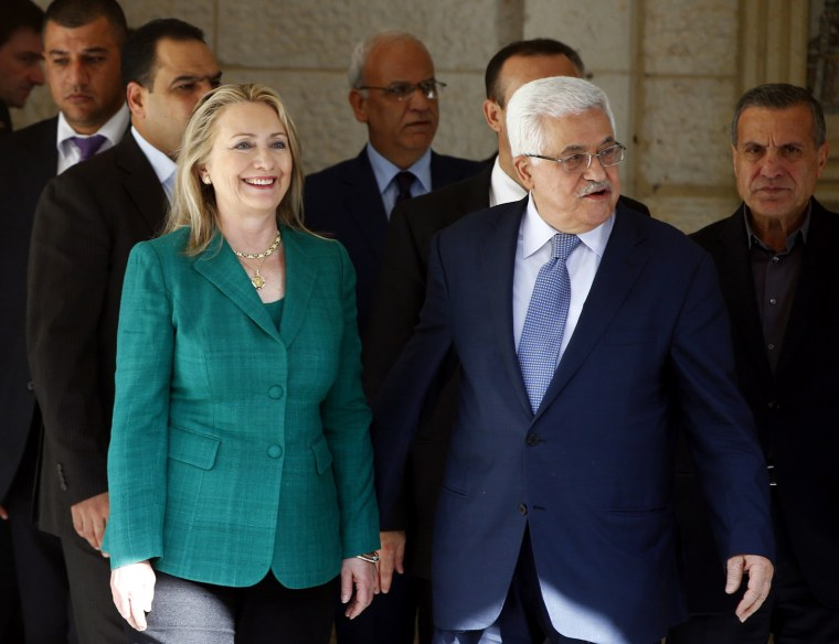 Image: US Secretary of State Clinton walks with Palestinian President Abbas after their meeting in the West Bank city of Ramallah