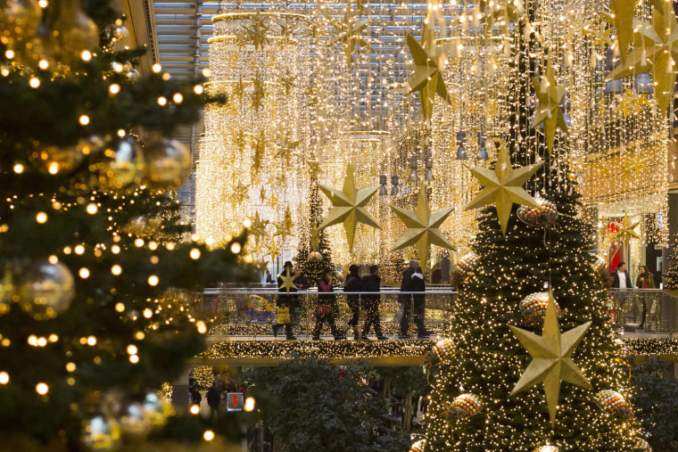 Image: People walk in a shopping mall that is decorated with Christmas lights in Berlin