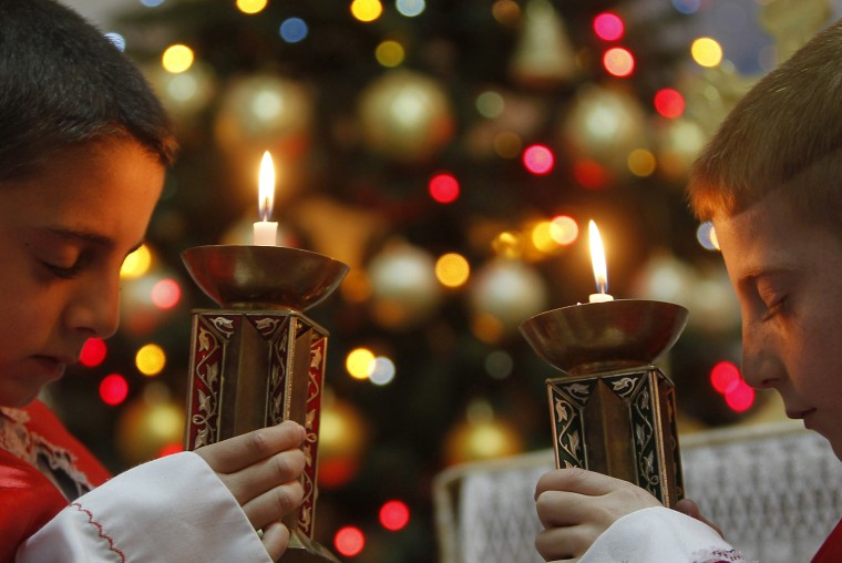 Image: Iraqi boys pray for peace in Iraq and Syria during Mass a day before Christmas Eve in Amman