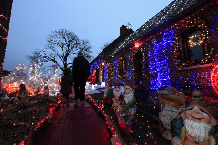 Image: People look at Christmas decorations at the home of Virginie and Jessy in Paillencourt, near Cambrai