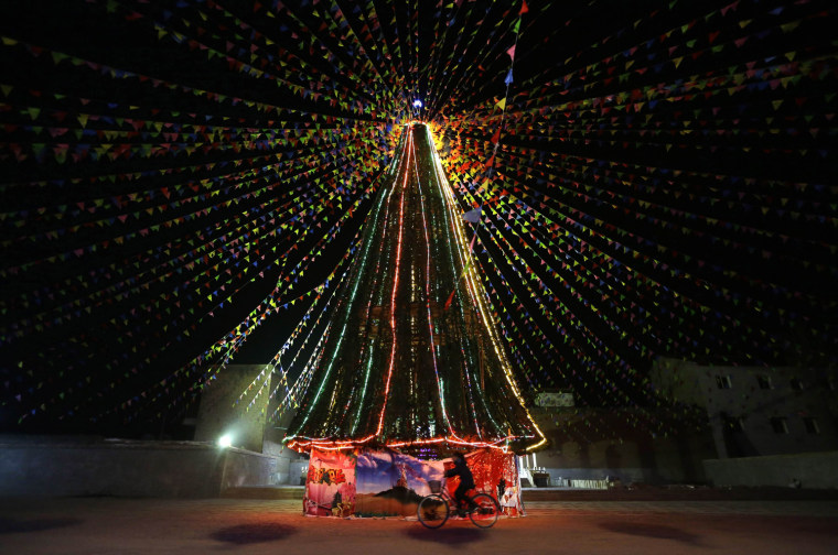 Image: A woman cycles past a Christmas tree outside a Catholic church in Xiliulin village