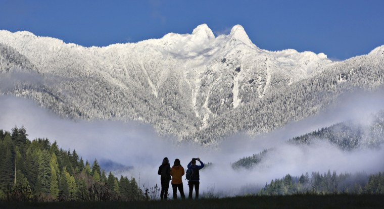 Image: Visitors to Capilano Park look out at the pointed peaks of The Lions covered in snow in North Vancouver