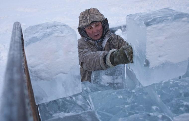 Image: Ruslan, 35, loads blocks of ice onto a truck outside Yakutsk
