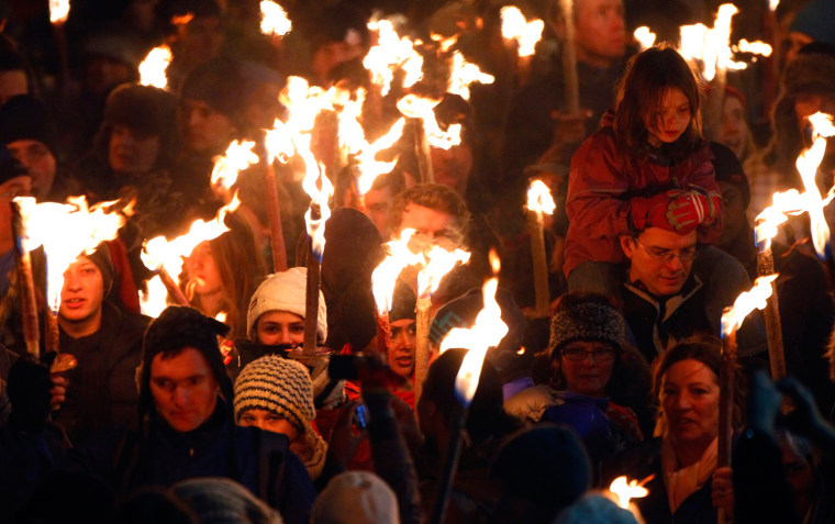 Image: People walk down North Bridge carrying lit torches during the annual torchlight procession to mark the start of Hogmanay (New Year) celebrations in Edinburgh, Scotland