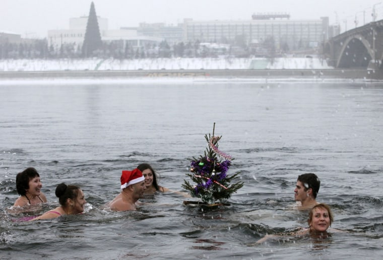 "Image: Members of the Cryophil amateur winter bathing club swim with a ""New Year tree"" in the Yenisei River as they celebrate the upcoming new year in Russia's Siberian city of Krasnoyarsk"