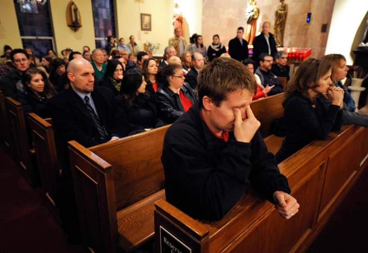 Image: Mourners gather inside the St. Rose of Lima Roman Catholic Church at a vigil service for victims of the Sandy Hook Elementary School shooting  in Newtown