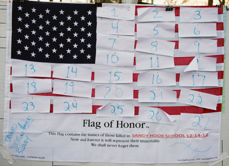 Image: A flag hanging in the business area of town waits for victims' names on December 15, 2012 in Newtown, Connecticut.