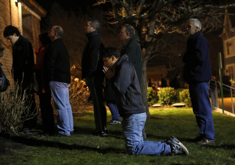 Image: People pray and stand outside the overflow area of a vigil at the Saint Rose of Lima church in Newtown, Connecticut