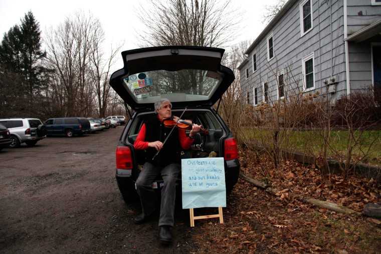 Image: Man plays a violin along Church Hill Road in Newtown, Connecticut