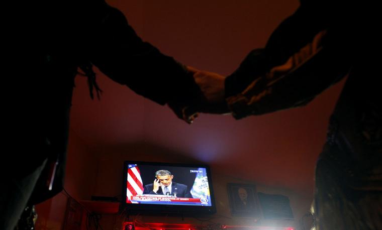 Image: People hold hands in a bar near Sandy Hook Elementary School as U.S. President Obama speaks in Newtown