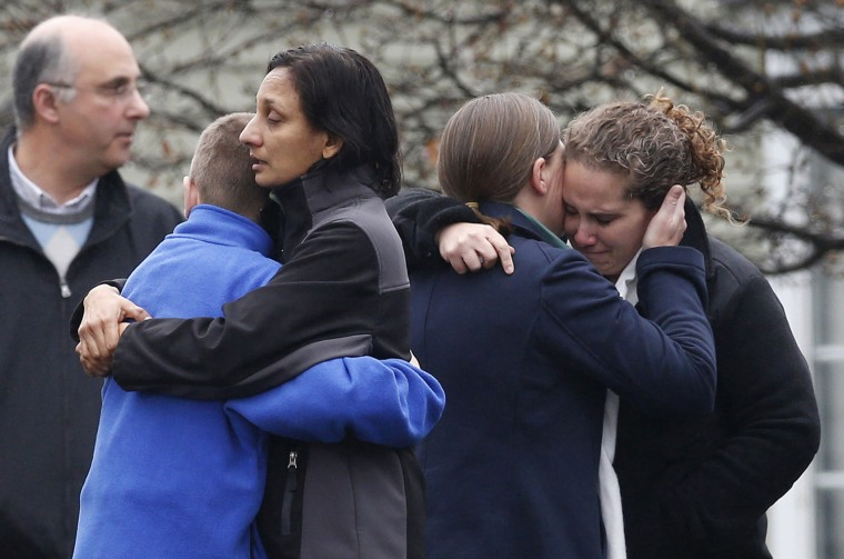 Image: Mourners embrace as they leave the Honan Funeral Home, where the family of six-year-old Pinto is holding his funeral service, in Newtown