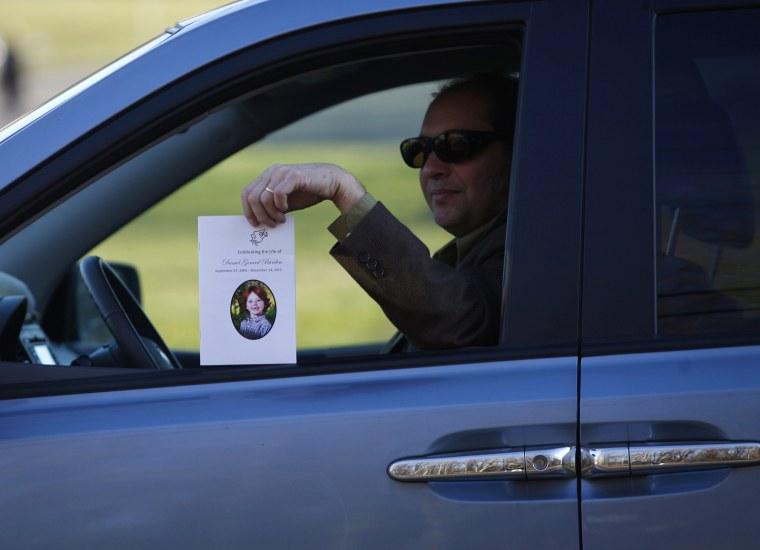 Image: Motorist holds obituary for Sandy Hook Elementary School shooting victim Daniel Barden in Newtown
