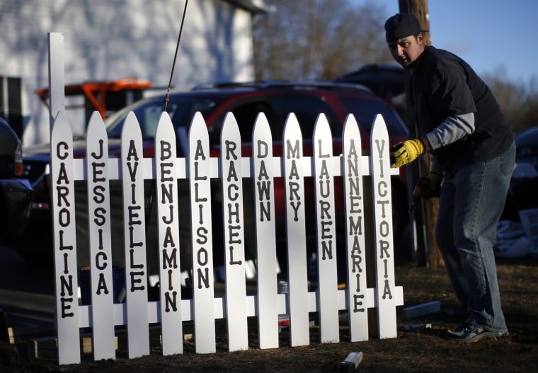 Image: Mike Garbowski begins to erect a fence he built that will bear the names of all of those killed in the December 14 shootings at the Sandy Hook Elementary School in Sandy Hook village in Newtown