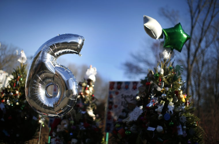 Image: A number 6 balloon left for one of the six-year-old victims of the December 14 shooting at the Sandy Hook Elementary school hangs in a makeshift memorial outside the school in Sandy Hook village in Newtown