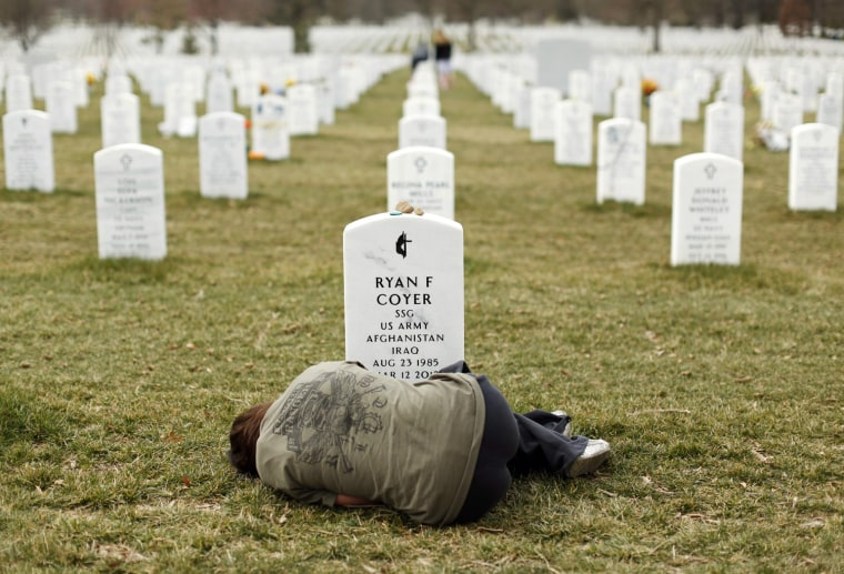 Image: Lesleigh Coyer, 25, of Saginaw, Michigan, lies down in front of the grave of her brother, Ryan Coyer, who served with the U.S. Army in both Iraq and Afghanistan.