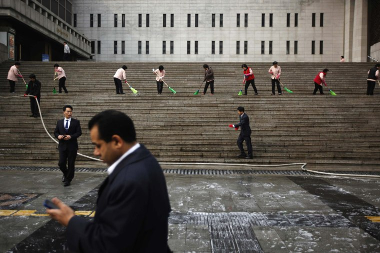 Image: Cleaners clean the stairs as a man using a mobile phone walks by at Sejong Centre for the Perfoming Arts in central Seoul