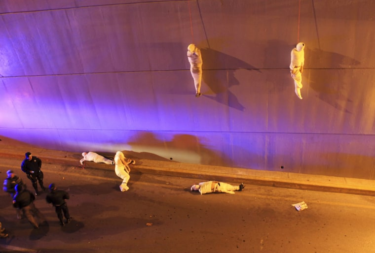 Image: The wrapped bodies of two dead people hang from an overpass as three more dead bodies lie on the ground in Saltillo