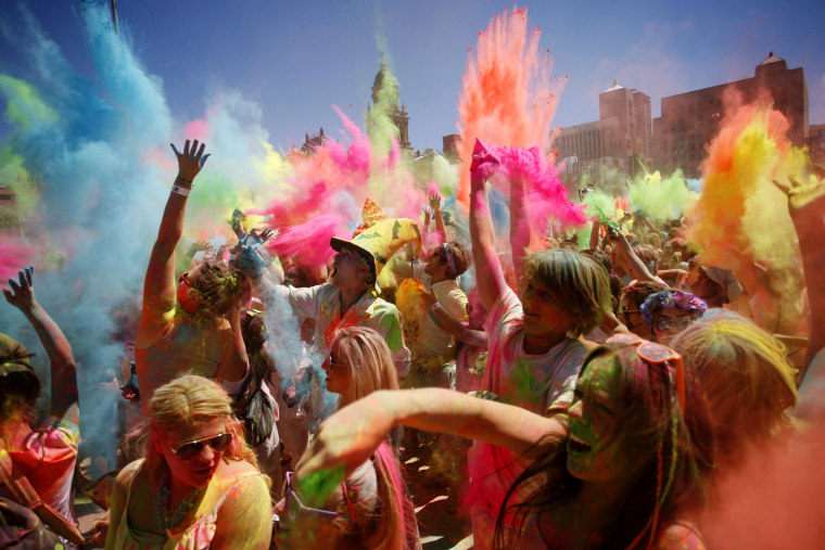 Image: Revellers are covered in coloured cornflour powder as they take part in the Holi One festival in Cape Town