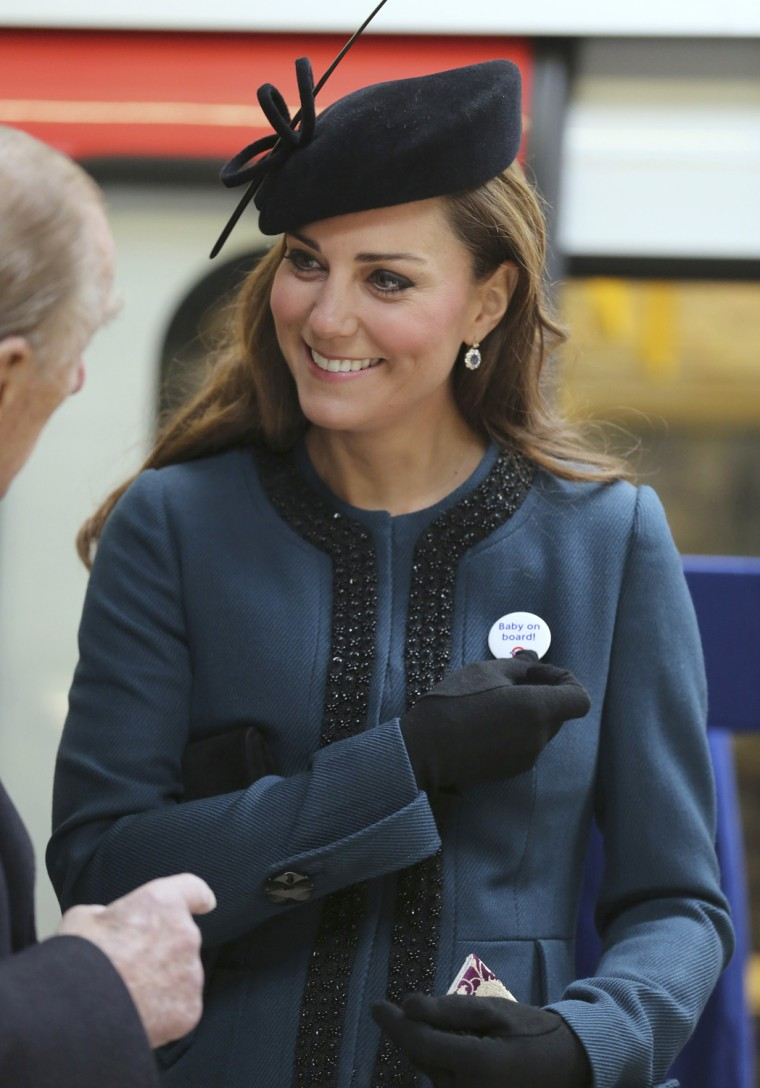 "Image: Britain's Catherine, Duchess of Cambridge holds a ""Baby on board!"" badge given to her during her visit to Baker Street underground station in London"