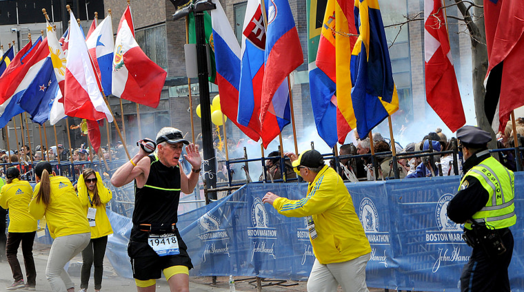 Image: Police and runners react to an explosion during the Boston Marathon