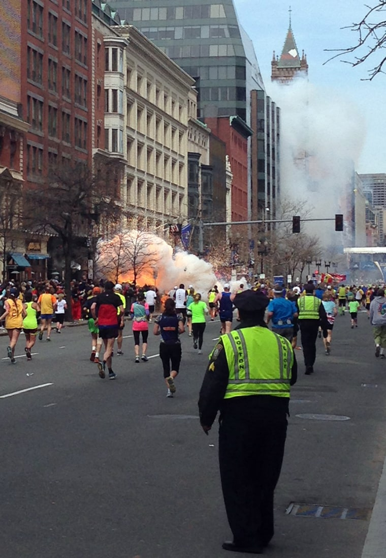 Image: Runners continue to run towards the finish line as an explosion erupts at the finish line of the Boston Marathon