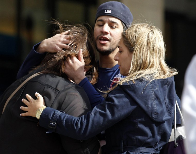 Image: People comfort each other after explosions went off at the 117th Boston Marathon in Boston