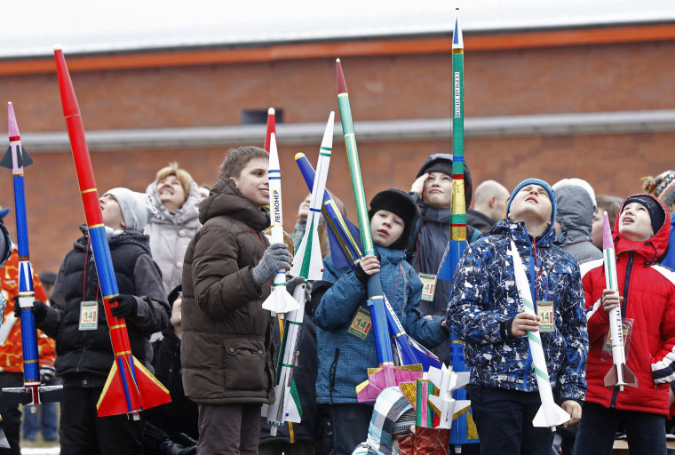 Image: Children hold self-made rocket models during a show in front of the Peter and Pawel Fortress in St. Petersburg