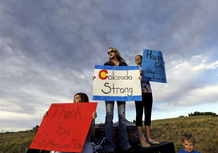 Image: From left, Black Forest resident Kristin Brown, whose family lost their home in the wildfire, is joined by Ashley Clipp, Kaitlyn Barlow and Ashley's son Jackson, 2, as they support first responders outside of a fire camp in Colorado Springs, Colo., on Sunday.