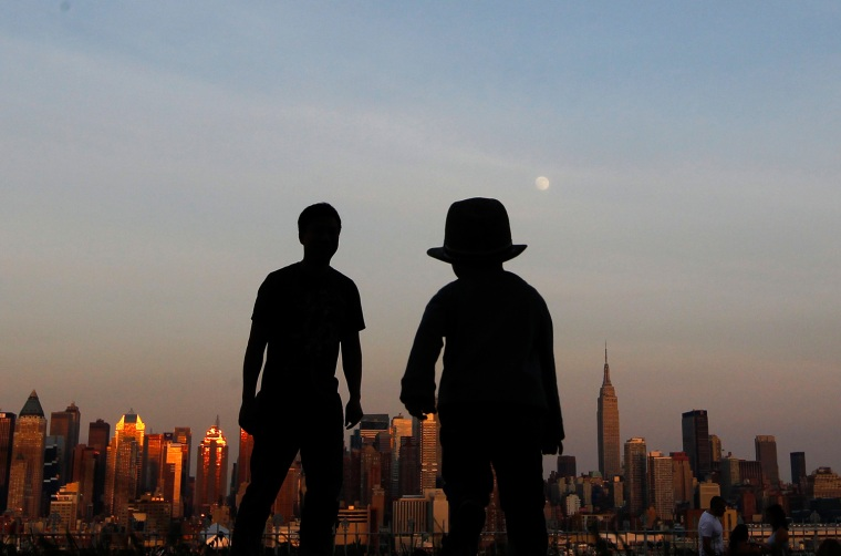 Image: A father and his son watch the moon rise over the skyline of New York from a lookout in Weekhawken, New Jersey